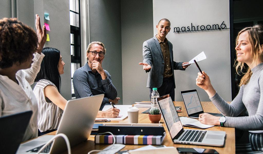 grupa osób siedząca przy stole w biurze. jeden z mężczyzn wygłasza prezentację po angielsku, jeden z uczestników zadaje pytanie
