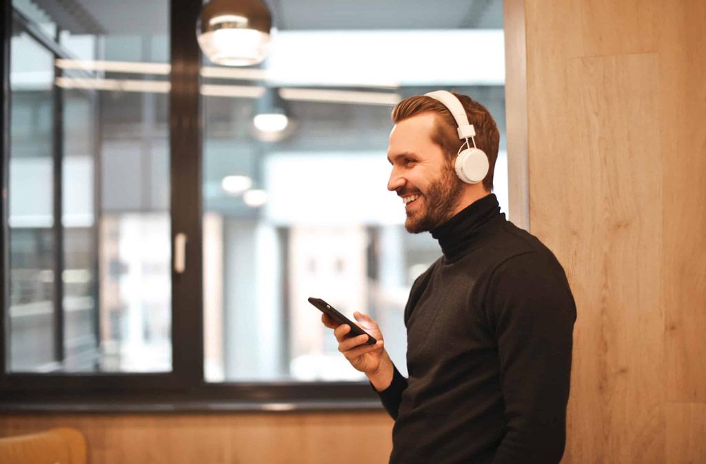 mężczyzna w słuchawkach słucha czegoś po angielsku i cieszy się, że rozumie angielski
