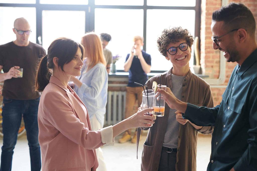 trzy osoby wznoszące toast i rozmawiające po angielsku w dużym, jasnym biurze razem z innymi współpracownikami