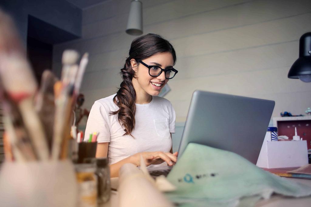 uśmiechnięta, młoda kobieta w okularach siedząca w biurze pisze list motywacyjny po angielsku na komputerze
