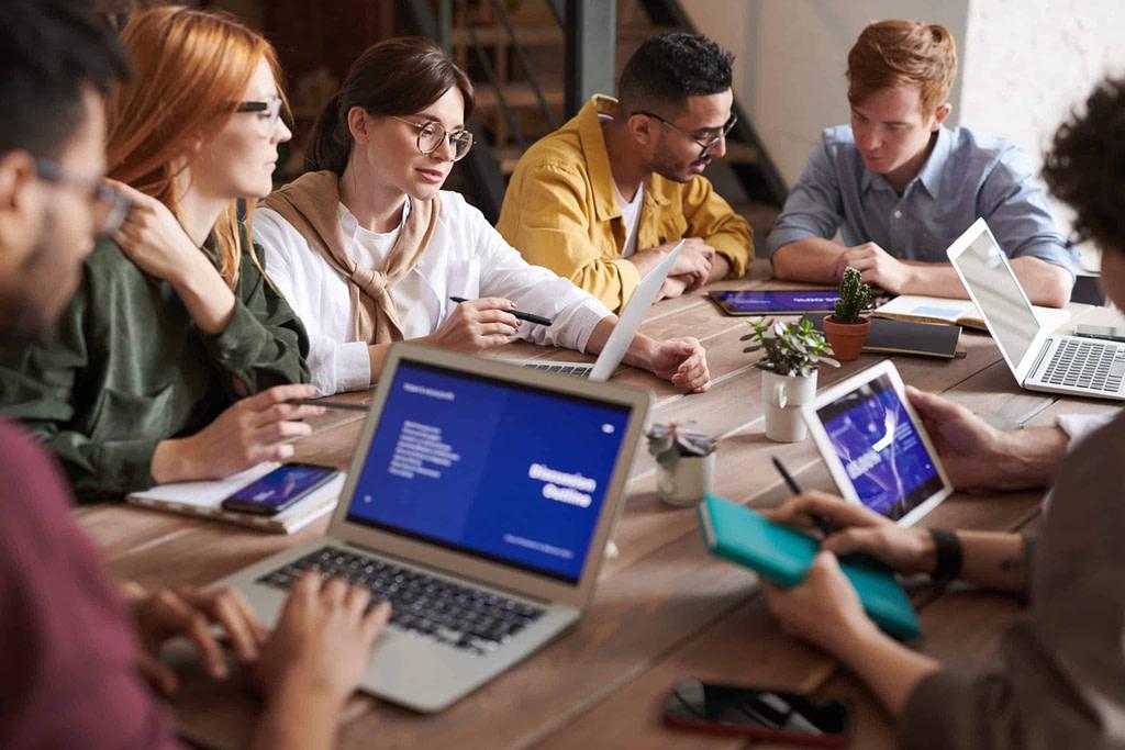 osoby siedzące przy stole w pracy podczas spotkania po angielsku i patrzące na wykresy na komputerach