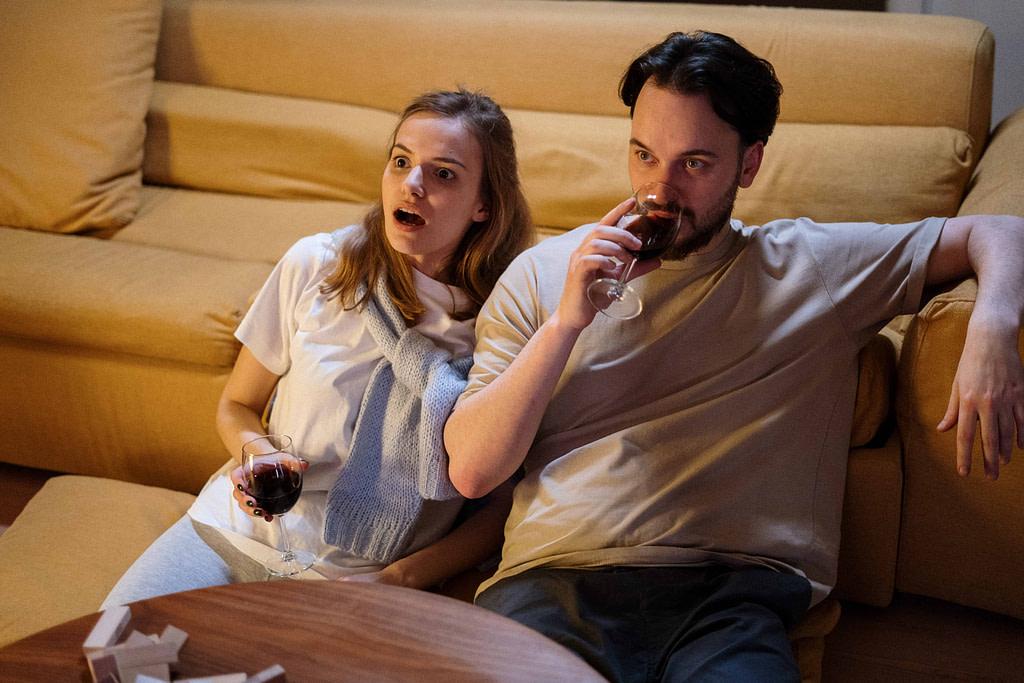 mężczyzna i kobieta oglądający na kanapie seriale i filmy po angielsku