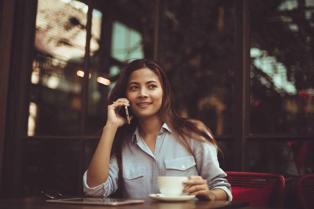 kobieta siedząca w biurze z filiżanką kawy. rozmawia przez telefon po angielsku i uśmiecha się do rozmówcy
