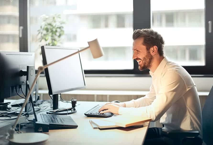 młody mężczyzna w eleganckiej białej koszuli w biurze. siedzi przy biurku i na komputerze pisze emaile po angielsku